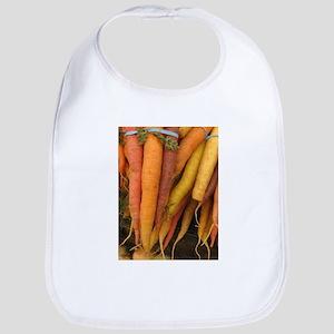 an assortment of long organic carrots in colors Bi
