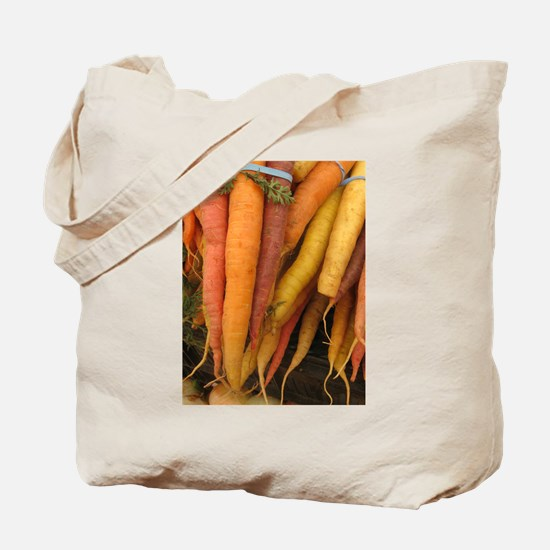 an assortment of long organic carrots in colors To