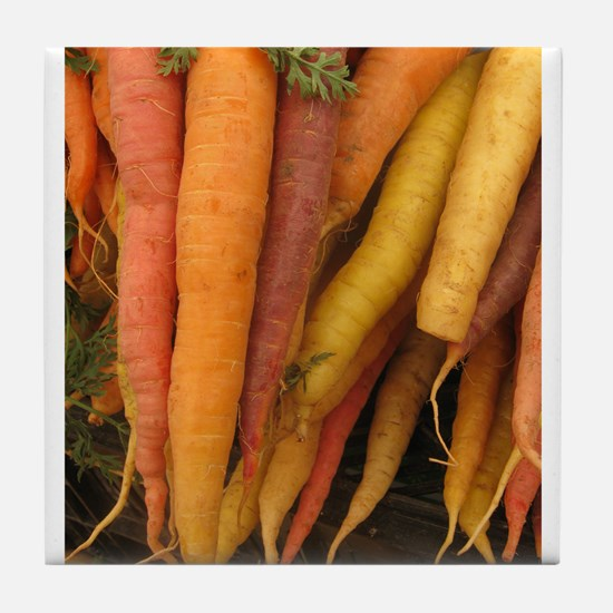 an assortment of long organic carrots in colors Ti