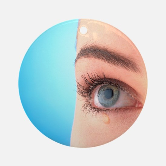 Close-up of a woman's blue eye with a tear-drop -