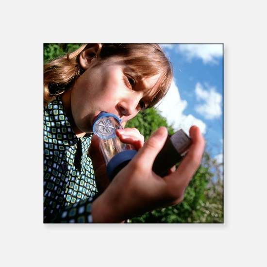 Girl with asthma uses an inhaler adaptor outdoors
