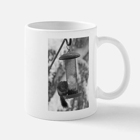 Squirrel at a birdfeeder in Winter Mug