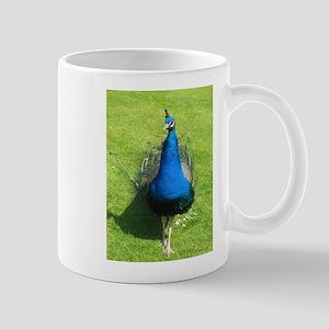 Peacock on grass Mug